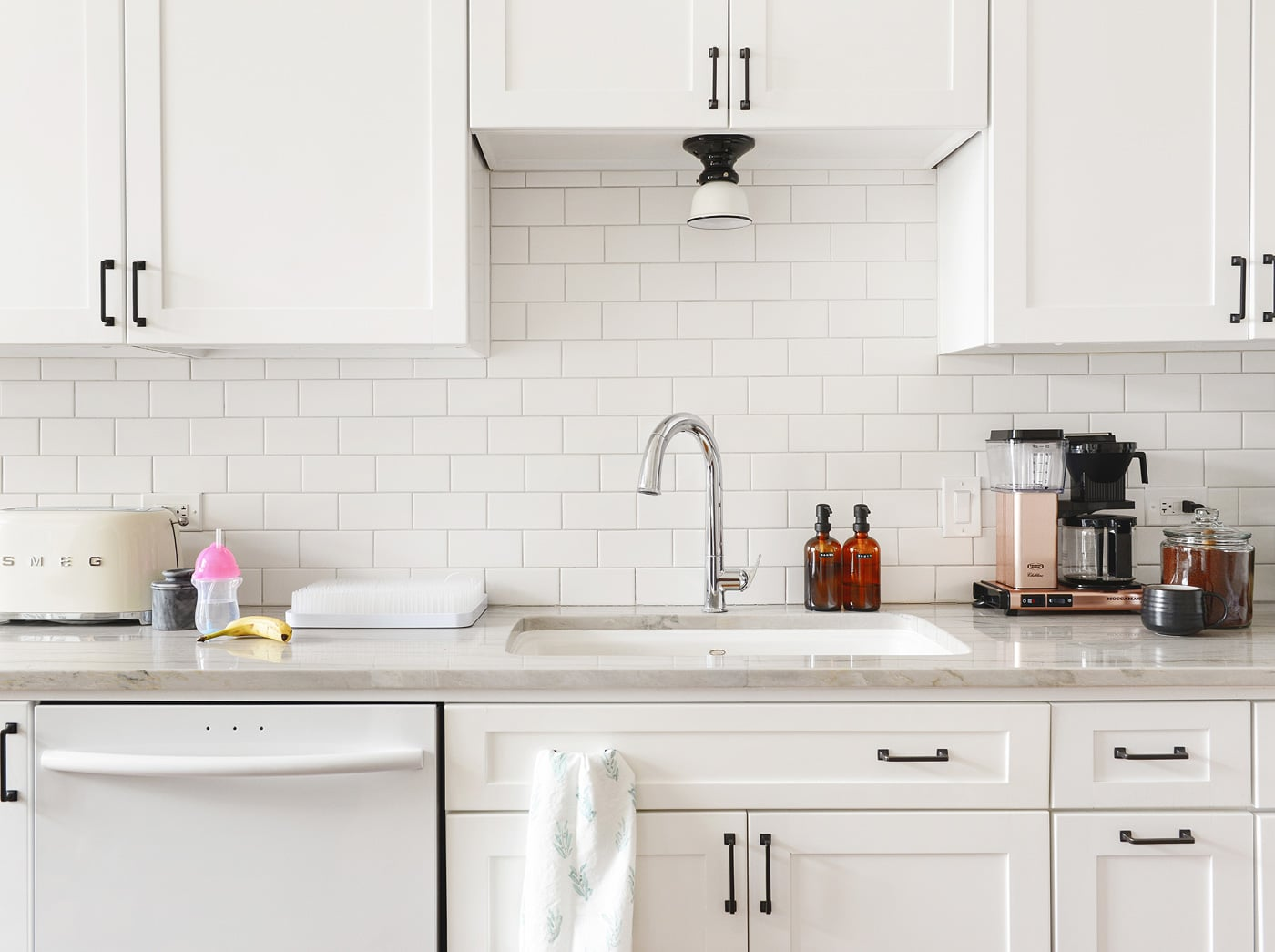 A white kitchen with amber soap pumps | via Yellow Brick Home